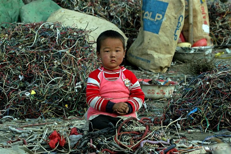 A small Chinese child sitting among cables and e-waste, Guiyu, China. Much of modern electronic equipment contains toxic ingredients. Vast amounts are routinely and often illegally shipped as waste from Europe, USA and Japan to countries in Asia as it is easier and cheaper to dump the problem on poorer countries with lower environmental standards. This practise exposes the workers and communities involved in dismantling e-waste to serious, environmental problems, danger and health hazards. Greenpeace is strongly urging major manufactures to exclude toxic materials from their products.